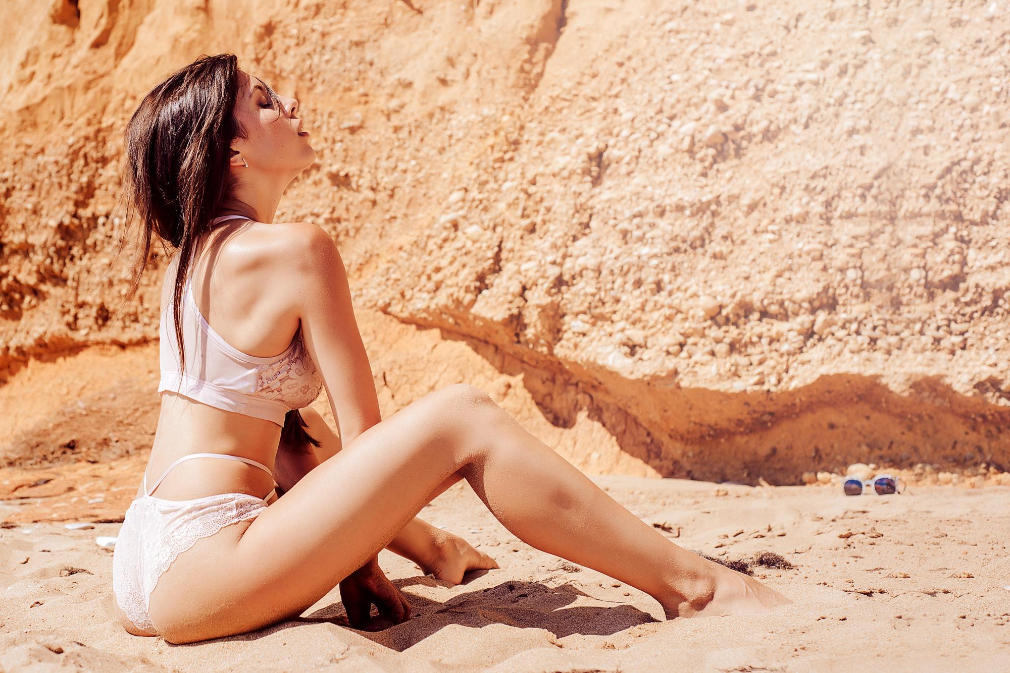 女性が砂浜で下着姿になっている