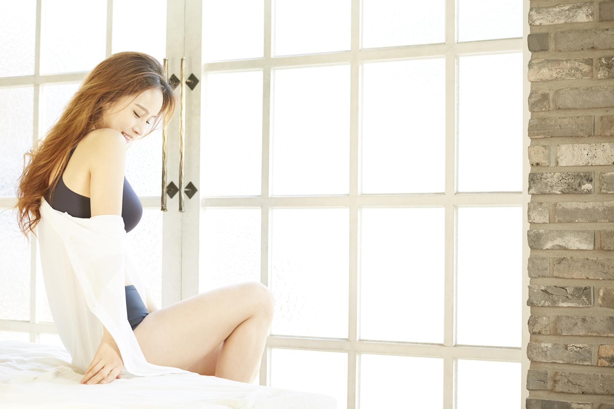 窓の前に立つノンワイヤーを着用している女性