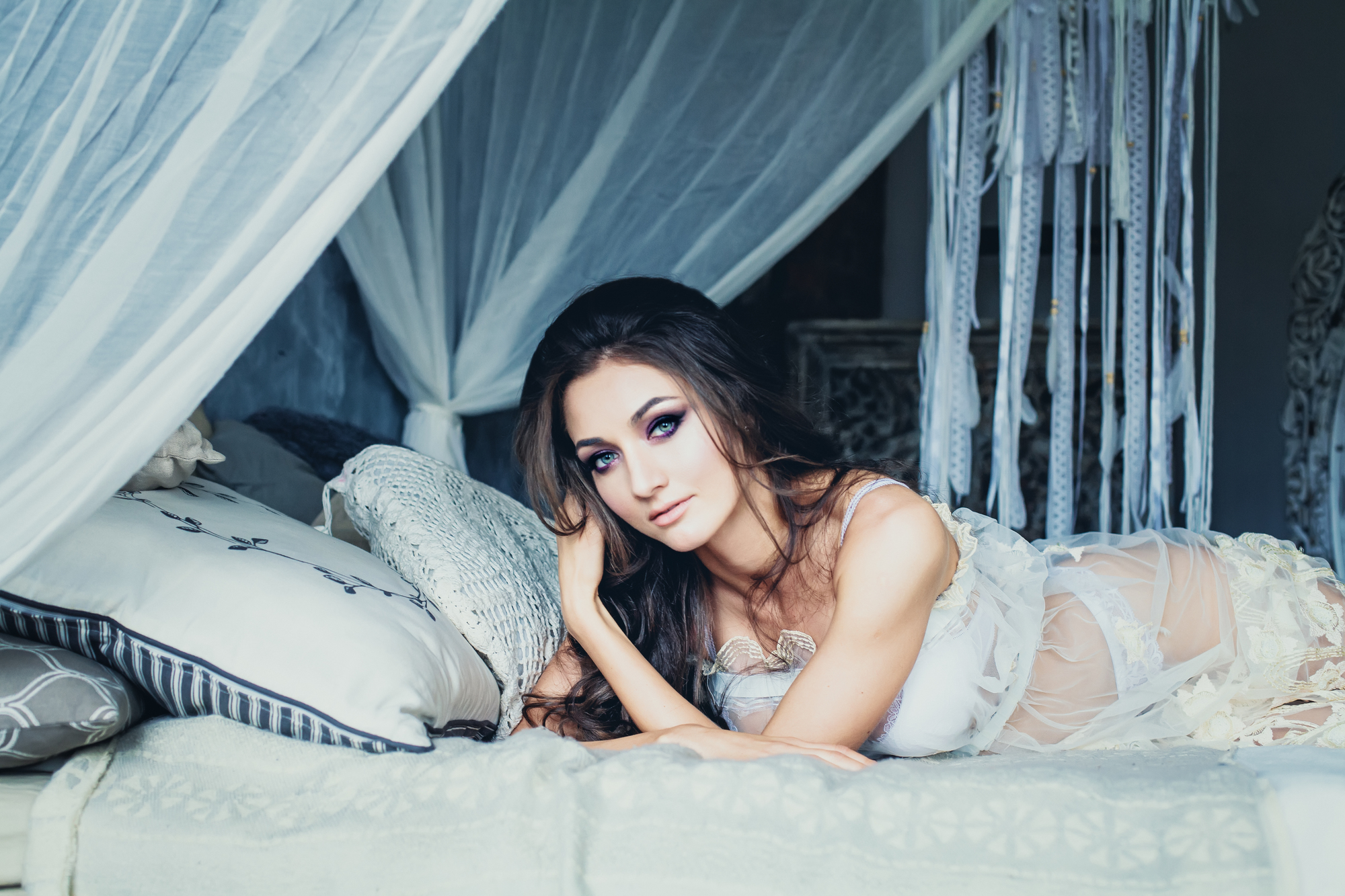 白いベッドの上で横向けになっている女性
